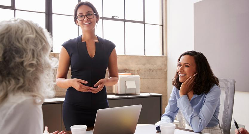 Women talking around table at office.