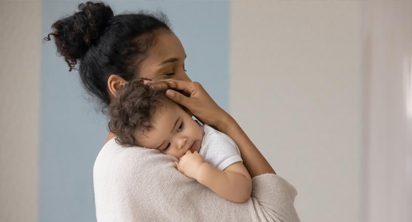 Mother holding infant child.