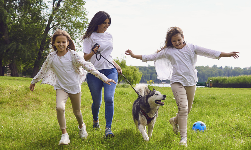 Mother and daughters running in park with family dog.