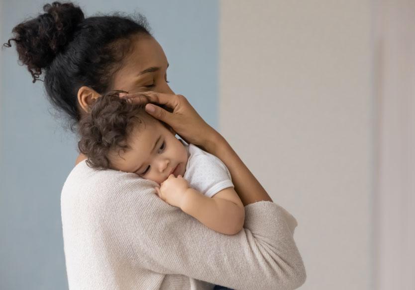 caring biracial mom hug